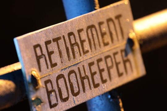 "A sign reserving a parking space in the back of Arlington High School for the ""retirement bookeeper."" The word bookkeeper is the only word in the english language to have three consecutive repeating letters with no hyphens--except in this case. December 17, 2011."