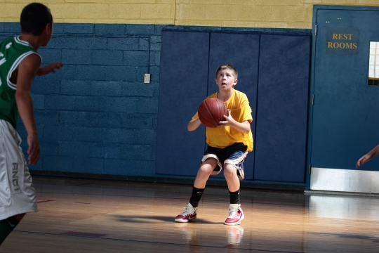 A player at the Fidelity House basketball camp takes a wide open shot during a game in the Arlington Catholic gymnasium. June 28, 2012.