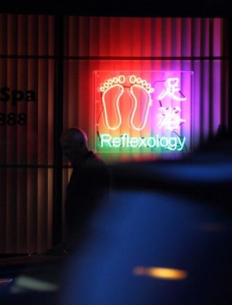 A man walks past a sign advertising reflexology on Massachusetts Avenue. August 24, 2012.