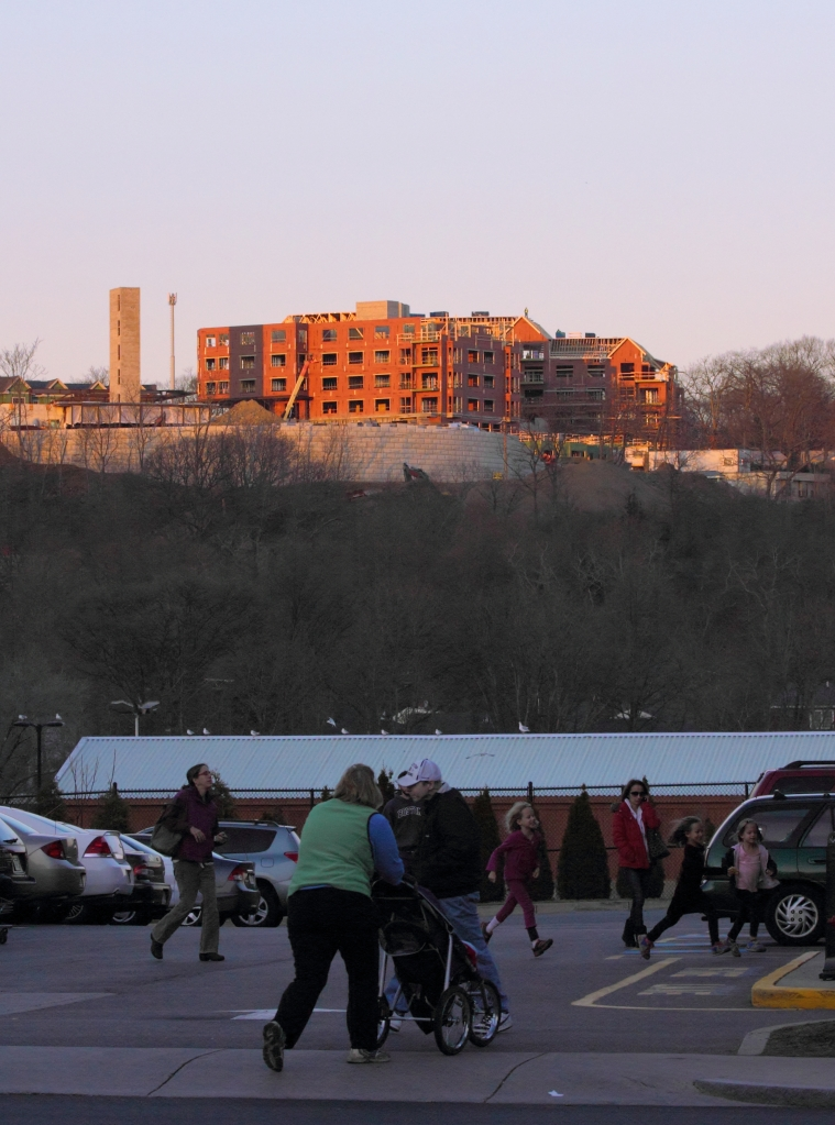A worker stands in the sunset atop the new construction at the former Symmes site as the rest of the people Arlington below go about their business.December 14, 2012.