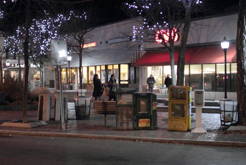 A few people walk around Arlington Center in the chilly night air.December 6, 2012.