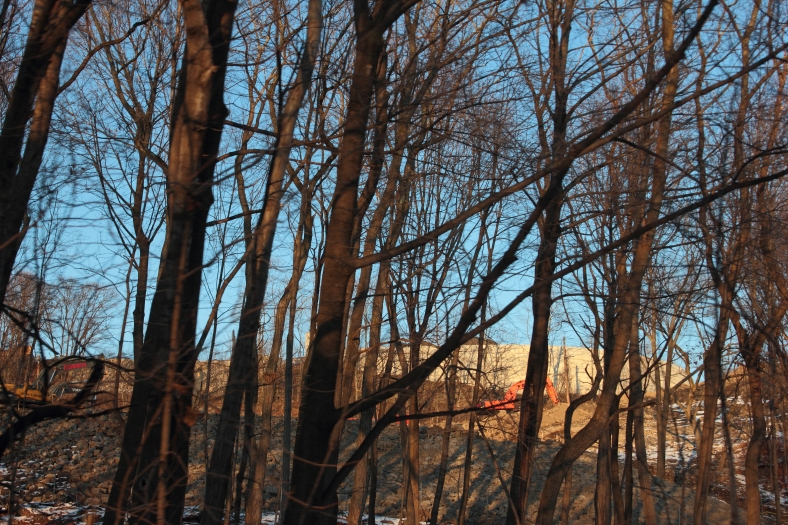 Blue sky and construction at the former Symmes site can easily be seen up through the wooded area that seems to be getting thinner and thiner.January 6, 2013.