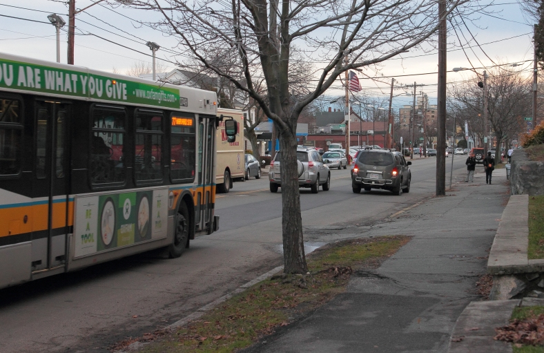The 77 bus bears down on an SUV driving slowly past the bus stop due to a flat tire.January 14, 2013.
