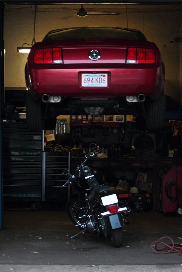 A motorcylcle is parked under a Mustang in the garage of Brown Automotive on Massachusetts Avenue.August 31, 2012.