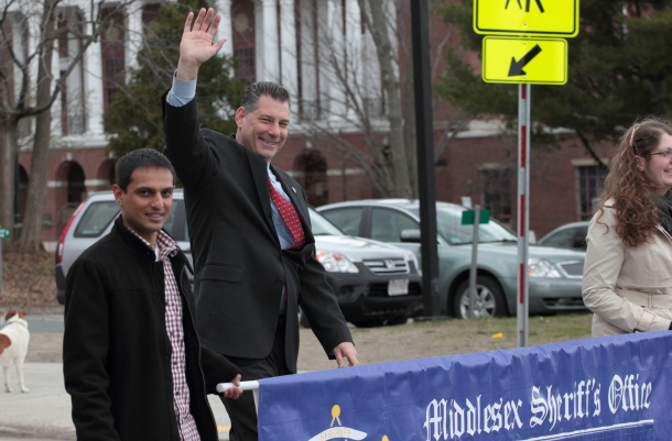 Middlesex Sheriff Peter Koutoujian waves as he passes Arlington High School during the Patriots' Day Parade. April 14, 2013.