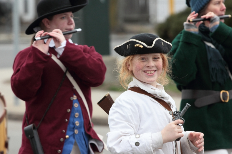 A member of the Menotomy Minutemen smiles as he processes down Massachusetts Avenue in the annual Patriots' Day parade. April 14, 2013.
