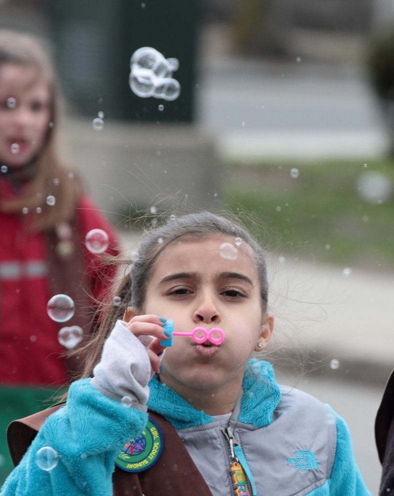 A girl scout blows bubbles as she marches with her troop in the 2013 Patriots' Day parade. April 14, 2013.