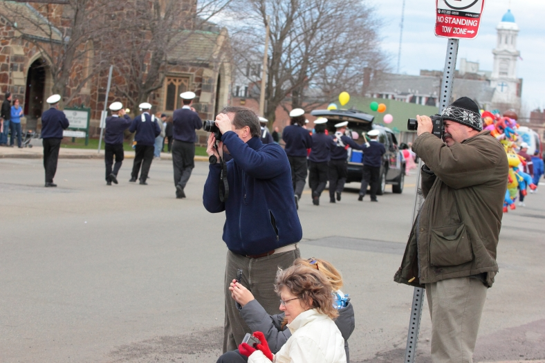 People snap their last photographs as the tail end of the Patriots' Day parade passes by. April 14, 2013.