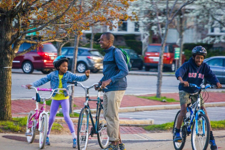 A father and his kids laugh as they wait to safely walk their bikes across the intersection of U.S. route 3 and MA route 60. April 28, 2013.