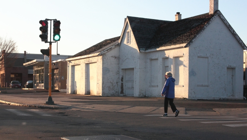 A woman shields her eyes against the setting sun as she crosses Schouler Court. April 21, 2013.