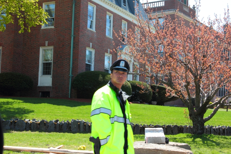 A police office from a neighboring town gazes into the distance as he works construction detail at the corner of Medford and Warren Streets. April 26, 2013.