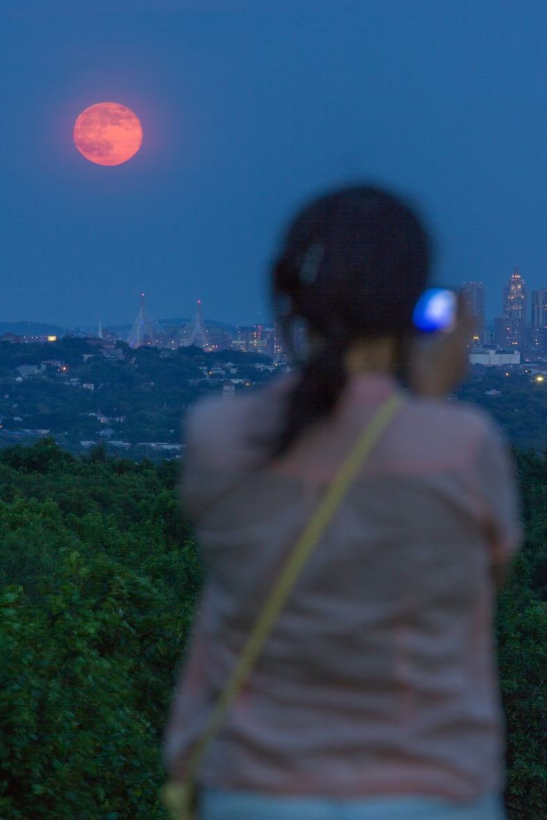 A woman at Skyline Park takes a picture of supermoon rising over Boston on the horizon. June 23, 2013.
