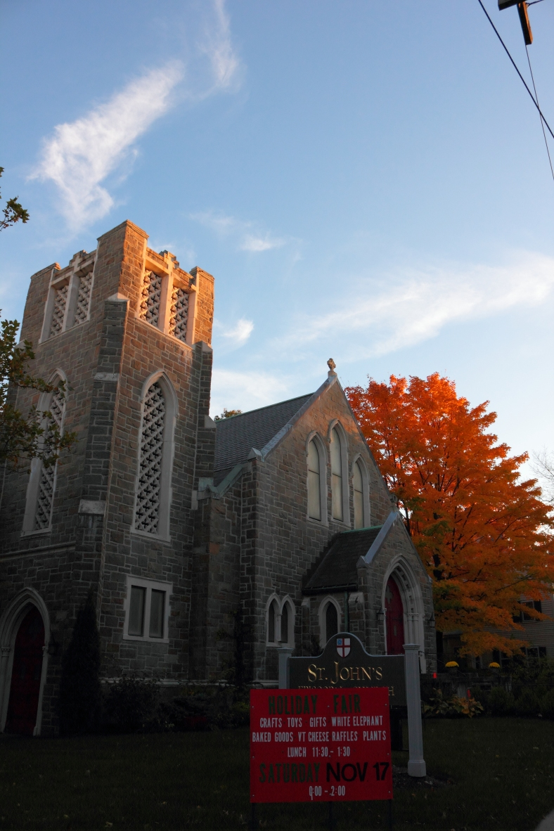 A sign outside St. John's Church on Pleasant Street advertises a fair while the setting sun illuminates the bell tower. October 20, 2012.