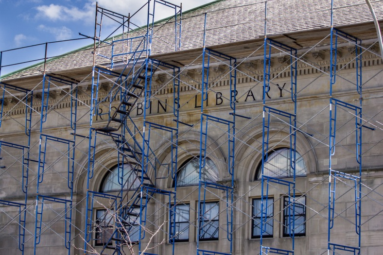 Scaffolding surrounding the original building of the Robbins Library during restoration and maintenance. July 5, 2013.