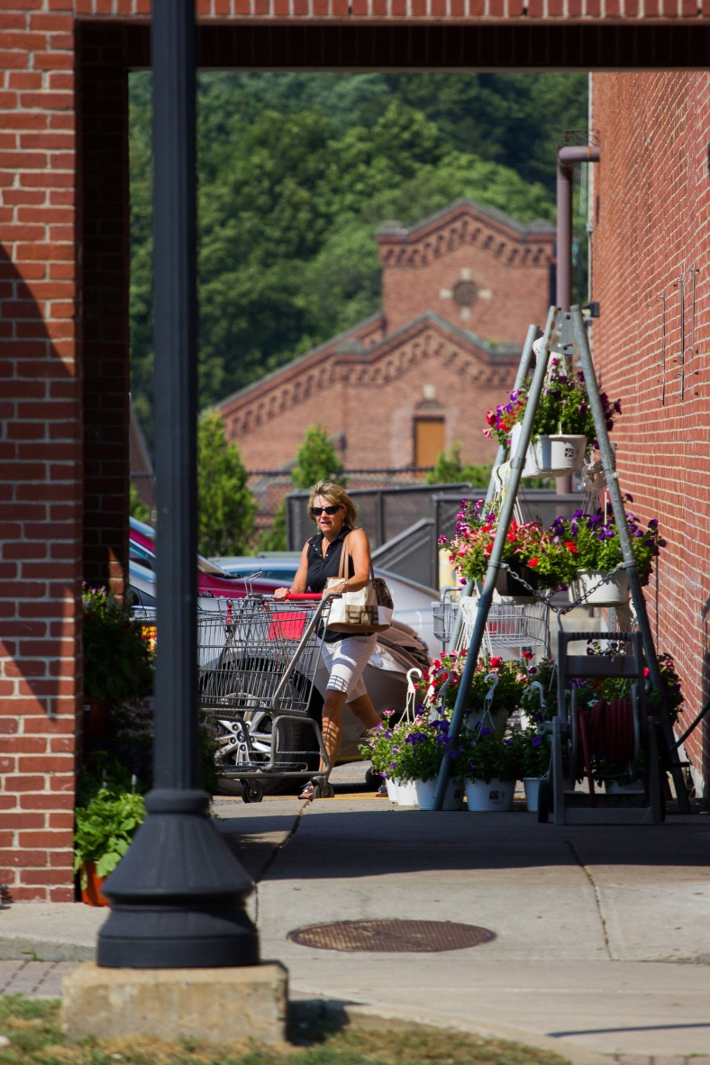 A woman pushes a cart into Stop and Shop, getting out of the 97˚ heat. July 19, 2013.