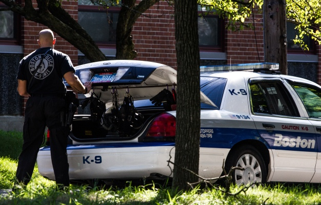 A Boston Police K9 unit officer gets supplies from the trunk of his cruiser during training exercises taking place in Stratton School. July 30, 2013.
