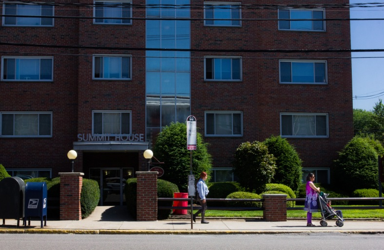 An apartment building looms over the westbound Lake Street bus stop in Capitol Square, East Arlington. August 14, 2013.