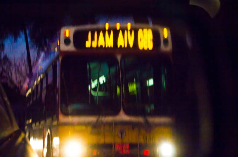 A bus to Alewife station comes up in the side view mirror on Massachusetts Avenue. August 20, 2013.