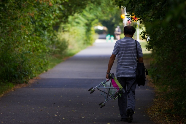 A man walks down the bike path carrying a stroller on a hot September day. September 12, 2013.
