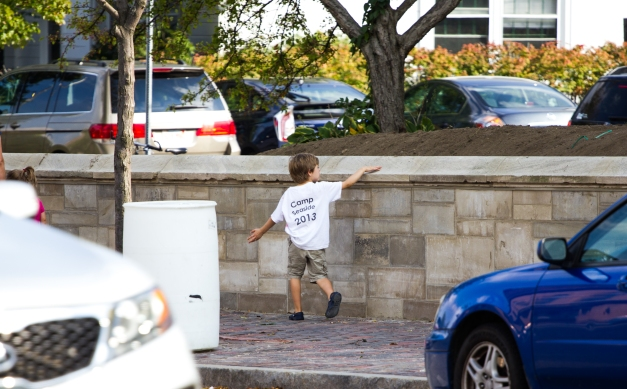 A young boy runs his hand along the old cap of a newly reconstructed wall at the Robbins Library. September 12, 2013