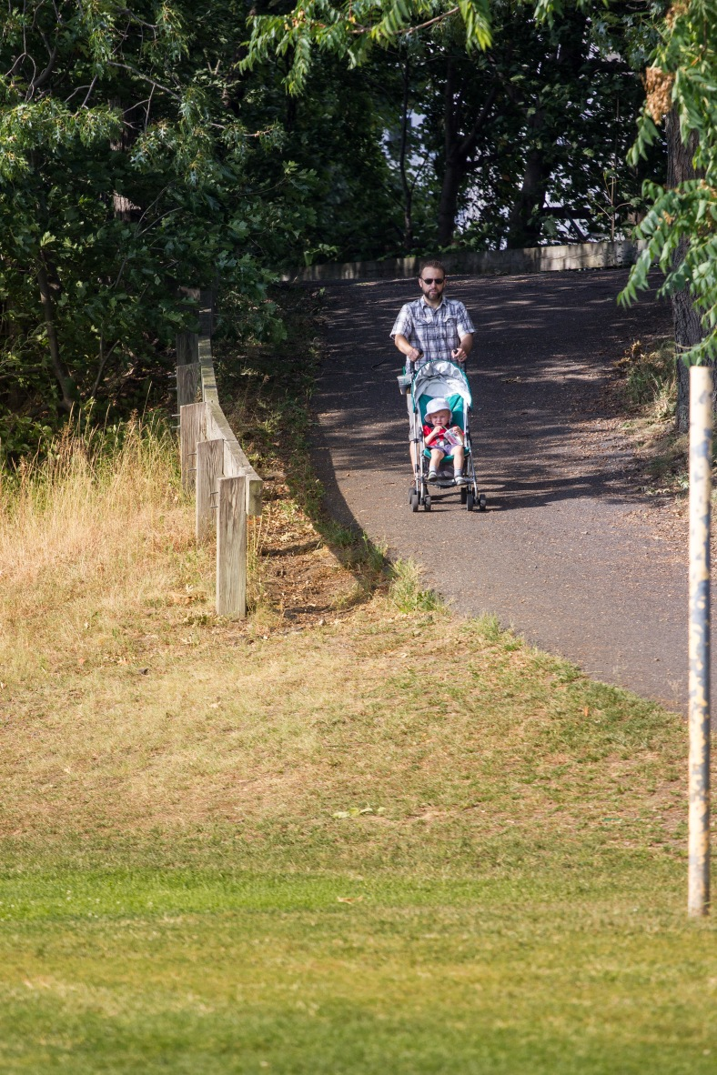 A man guides his child in a stroller down the ramp off the bike path to Spy Pond Field. September, 12, 2013.