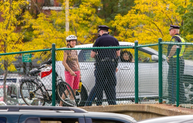 A cyclist talks with a police officer after she was involved in a traffic incident on Mystic Street. September 21, 2013.