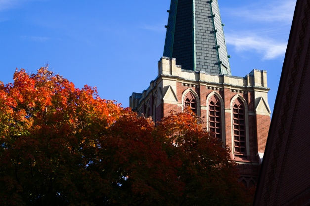Fall foliage illuminated by the afternoon sun next to the bell tower and steeple of the Church of St. Agnes. October 3, 2013.