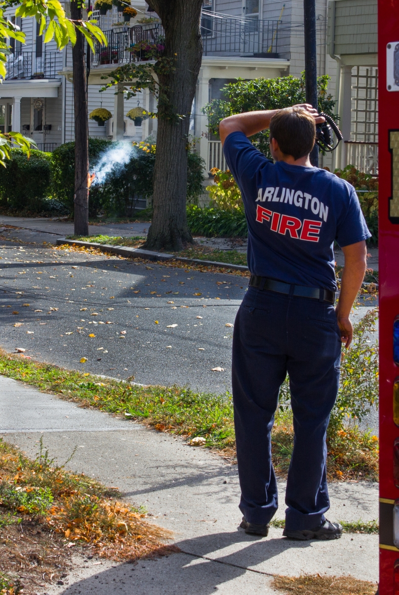 An Arlington firefighter watches as a small fire starts on a telephone pole as a result of downed power line on Freeman Street. October 22, 2013.