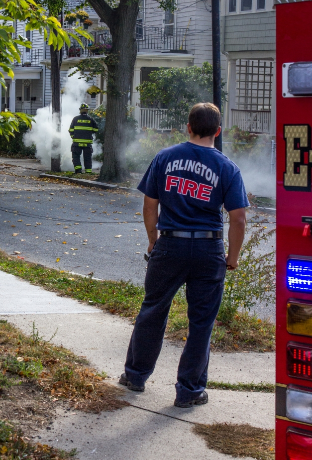 An Arlington firefighter puts out a fire caused by a downed power line before it gets out of hand. October 22, 2013.