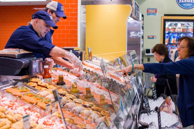 A woman points at the exact salmon steak she wants to buy during the opening hour of Arlington Whole Foods. September 18, 2013.