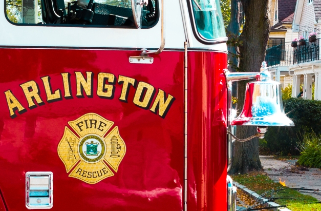 The shiny bell on an Arlington fire engine as it is parked across Freeman Street while responding to a downed power line (background). October 22, 2013.