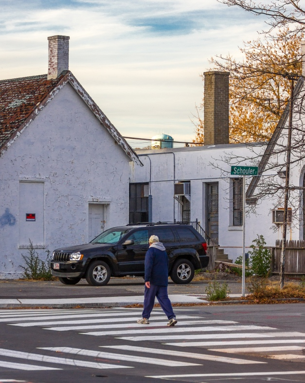 A man crosses Schouler Court while the green Turkey Hill water tower can be seen in the distance. November 15, 2013.