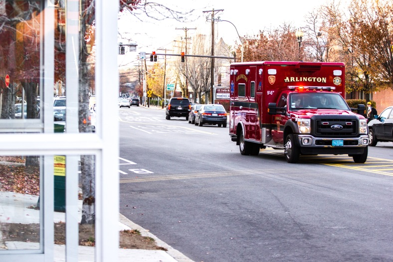 An Arlington Fire Department ambulance races down Massachusetts Avenue past a new bus shelter while responding to a call. November 15, 2013.
