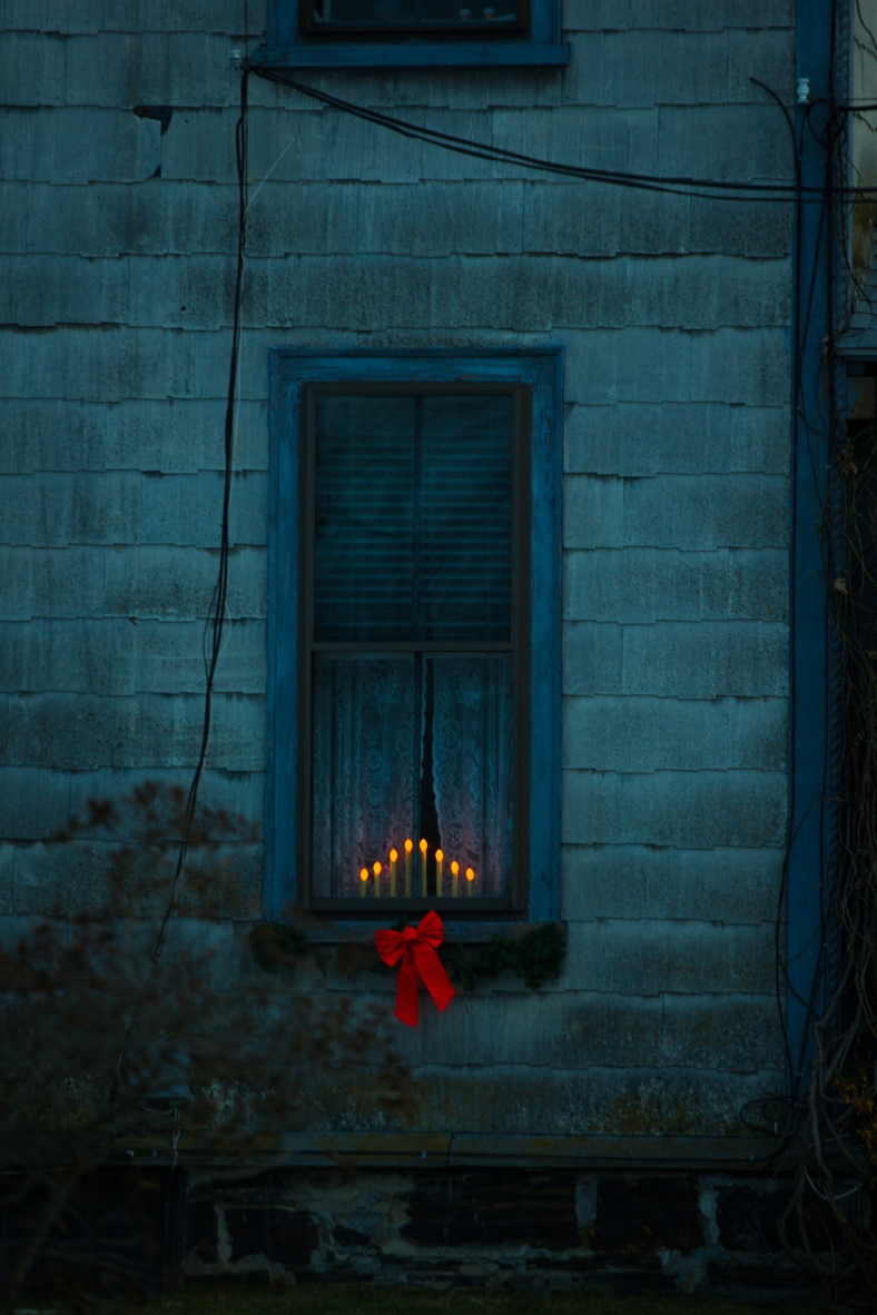 Electric candles and holiday decor brighten up a Warren Street home. December 24, 2013.