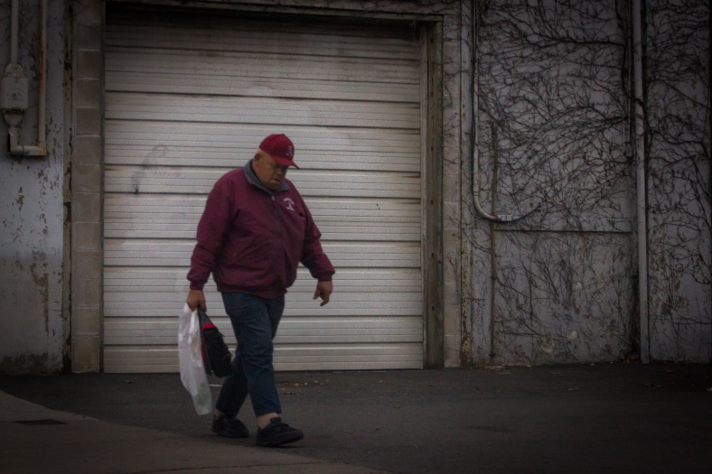 """Happy,"" who is known by many around town due to his work for the Recreation Department, walks down a deserted (due to an area-wide lockdown) Mill Street. April 19, 2013."