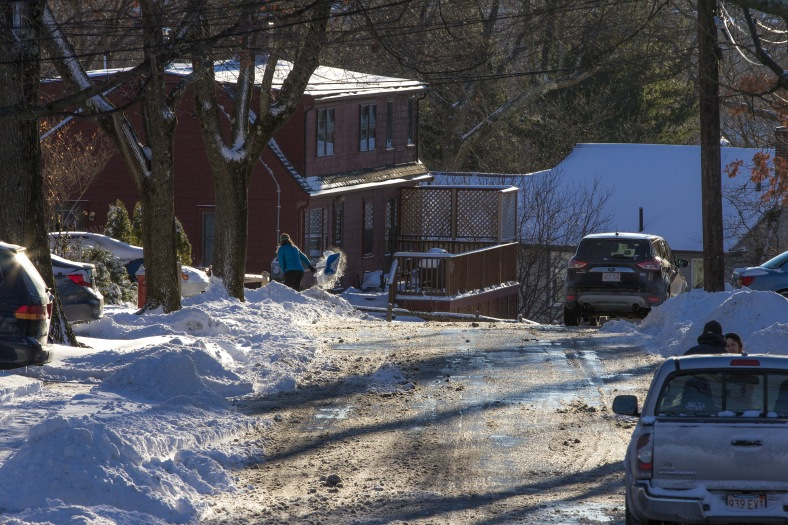 Neighbors stop to chat on Chatham Street while a woman shovels out her property down the way. January 3, 2014.
