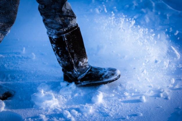 A woman kicks up snow as she walks across the Stratton School blacktop. January 3, 2013.