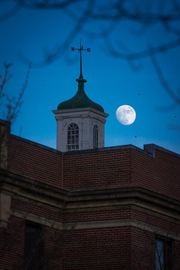 The moon rises over Arlington High School as it waxes toward a mid-month full moon. January 13, 2014.