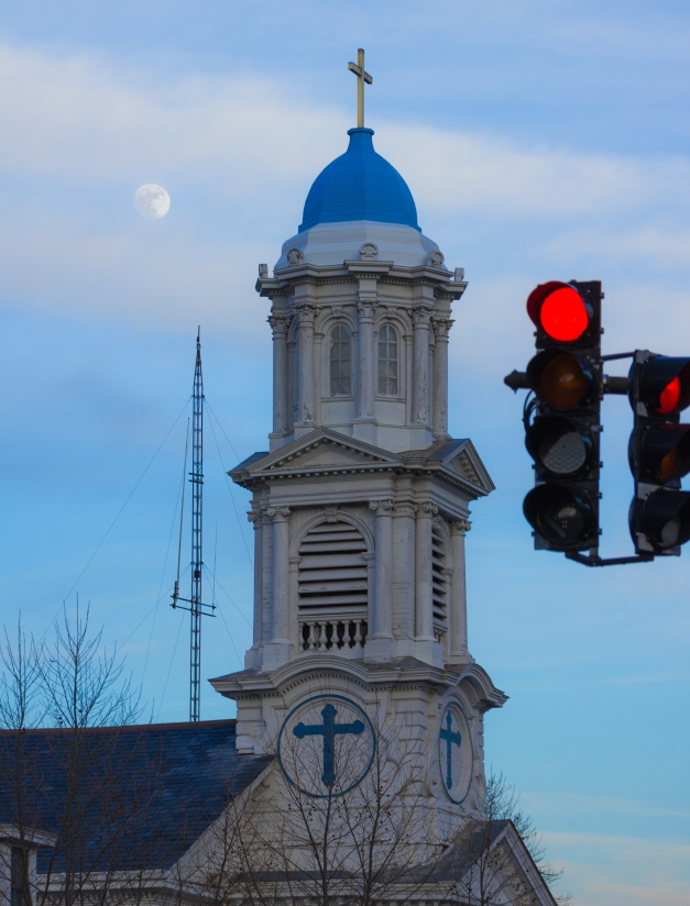 Behind two red lights at the intersection of Jason Street and Massachusetts Avenue, the Highrock Chruch, and behind that, the moon. January 13, 2014.