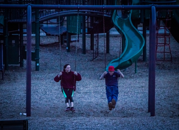 Teens enjoy the swings at the Robbins Farm Playground just after sunset. May 9, 2013.