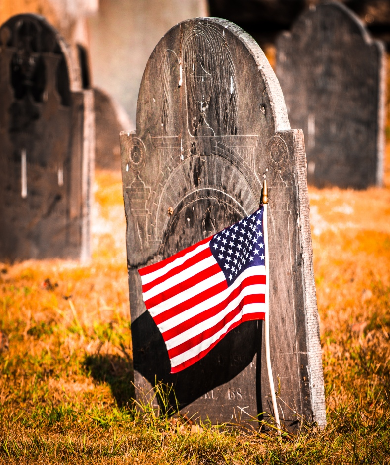 A headstone in the Old Burying Ground adorned with an American flag. September 12, 2013.