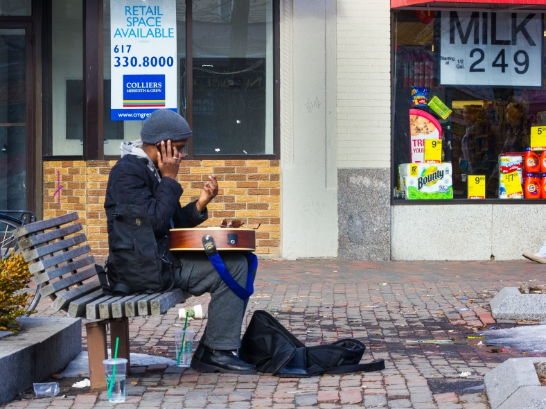 A man sits with guitar on lap in Arlington Center during a pleasantly warm March day. March 8, 2014. SC