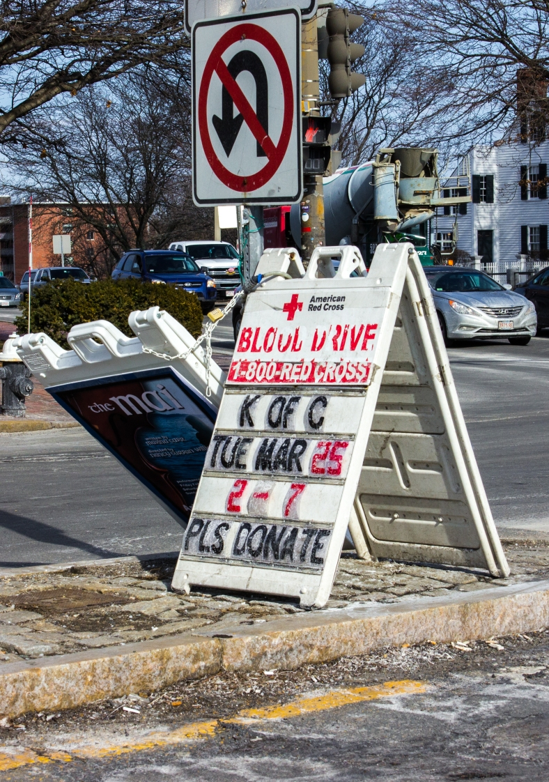 A sign in Arlington Center, battered by salting, sanding, and winter weather, solicits donations for a blood drive. March 14, 2014.