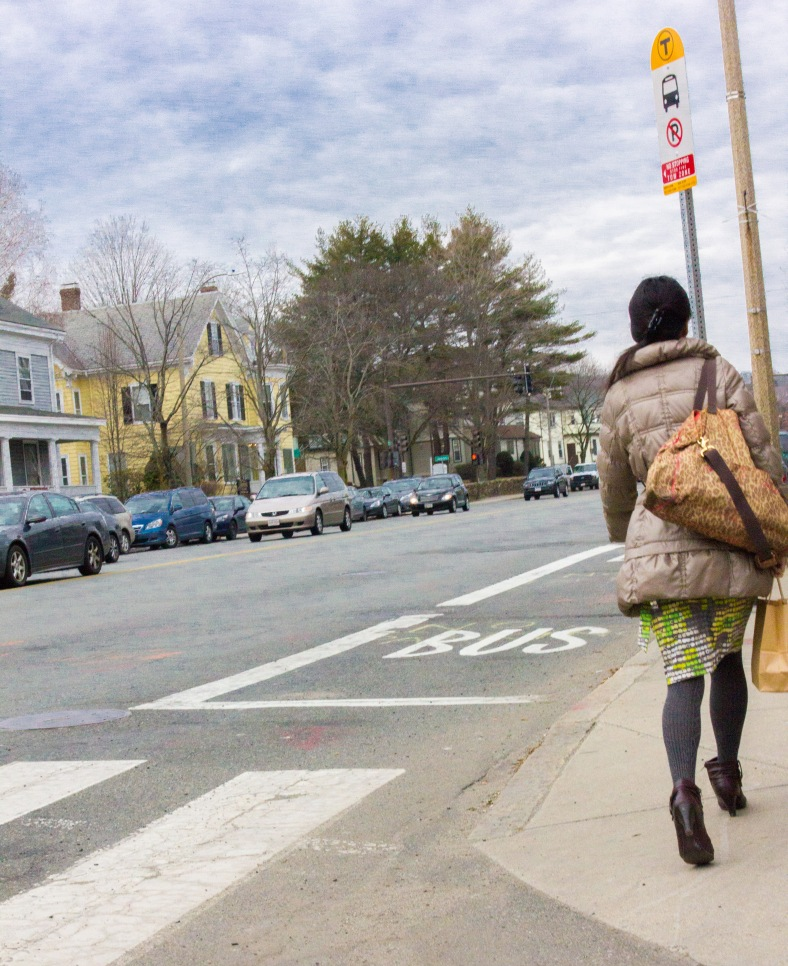 A woman walks past a bus stop on Massachusetts Avenue. March 28, 2014,
