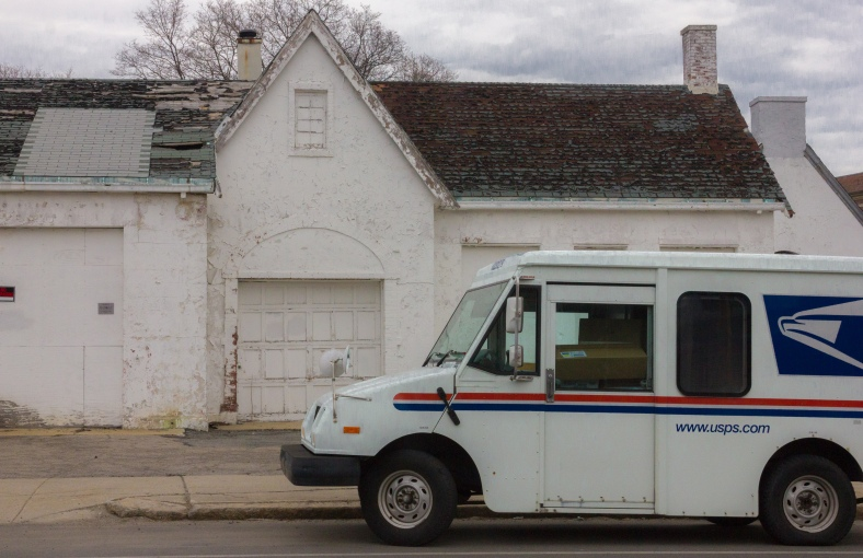 A mail truck parked outside a similarly colored building on Massachusetts Avenue. March 28, 2014.