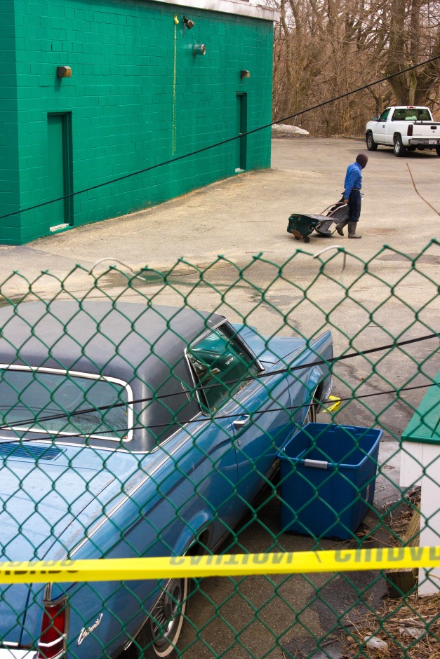 A man lugs car parts across the back lot of Dudley Street Auto Body. March 28, 2014.