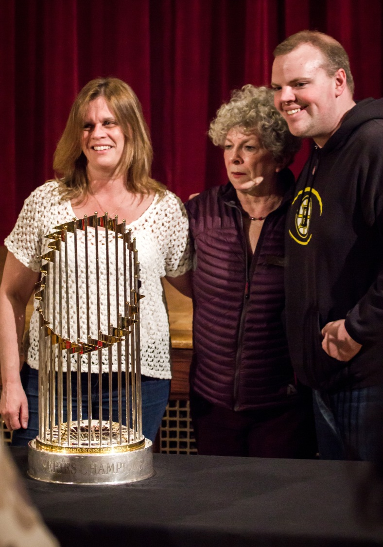 Women pose with State Rep. Sean Garballey and the World Series trophy from the 2013 championship season of the Boston Red Sox during a showing at Town Hall. March 29, 2014.