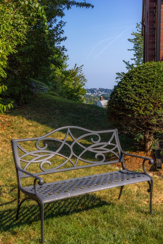 A bench in the front yard of a Richfield Road home offers views of the street, while out back there are views of Boston and its surrounds. September 11, 2013.