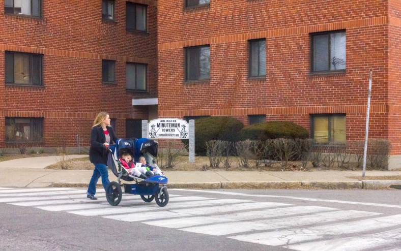 A woman pushes her two young children across Bates Road in front of Minuteman Towers. March 28, 2014.