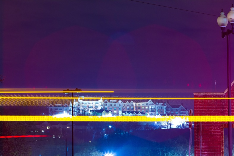 The lights of Arlington 360 shine bright as a 77 bus passes by on Massachusetts Avenue. May 2, 2014.